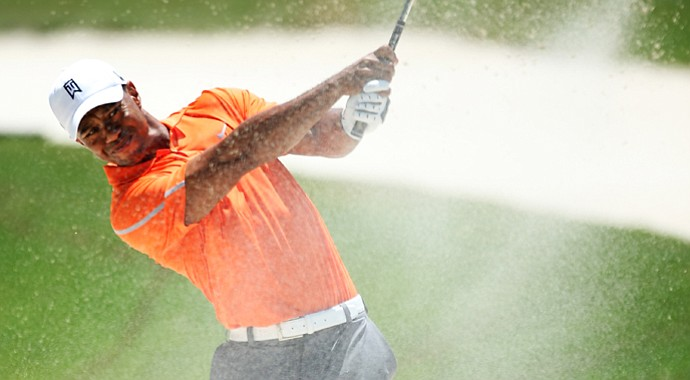 Tiger Woods plays his second shot from a bunker on the first hole during the first round of the Players Championship.