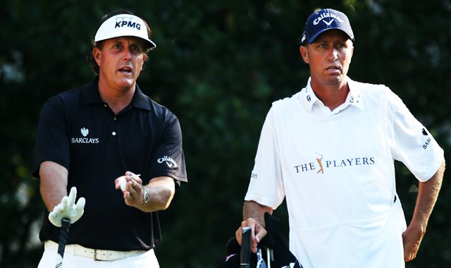Phil Mickelson and his caddie Jim Mackay stand on the 11th tee on Friday. Mickelson fired a 1-over 73 on Friday, sending himself home a bit earlier than expected.