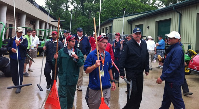 An army of Merion workers prepare to squeegee the course after 90 minutes of rain that suspended play on Thursday morning.