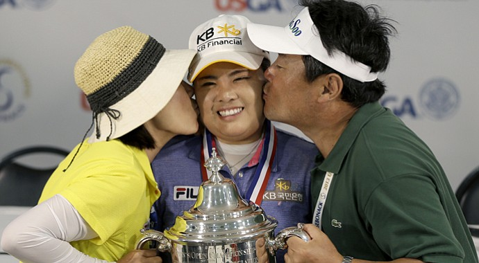 Inbee Park (center) poses for a picture with her trophy while her parents, Sungja Kim (left) and Gungyu Park, kiss her after she won the U.S. Women's Open.