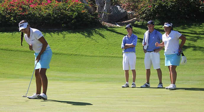 The West's Krystal Quihuis stands over a putt as teammates watch.