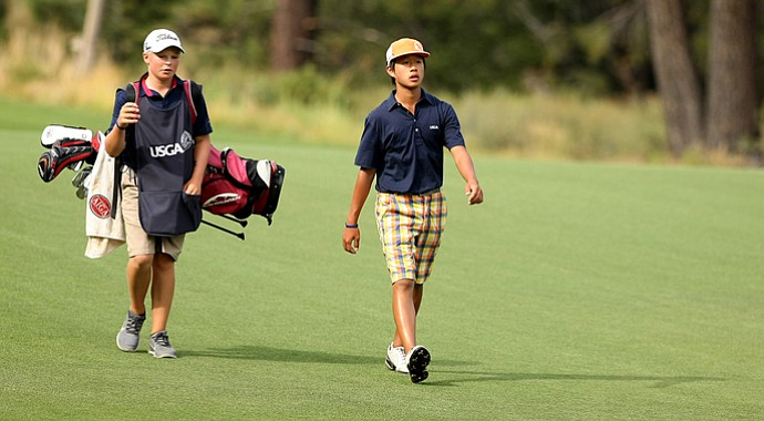 Shuai Ming Wong, 13, walks with caddie Frankie Capan, 13, up the 11th fairway during the 66th U. S. Junior Amateur Championship at Martis Camp Club.