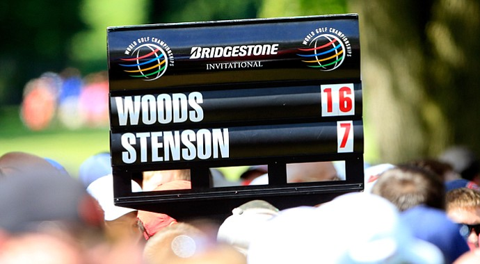 A standard bearer carries the scores of Tiger Woods and Henrik Stenson during the final round of the WGC-Bridgestone Invitational at Firestone Country Club.