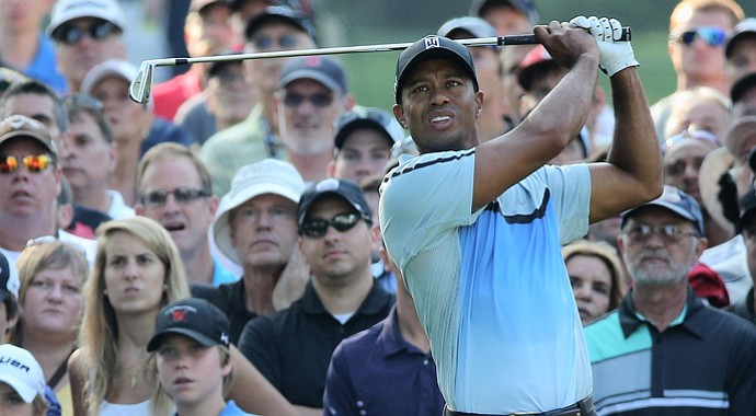 Tiger Woods watches his tee shot on the 11th hole during the first round of the 95th PGA Championship.