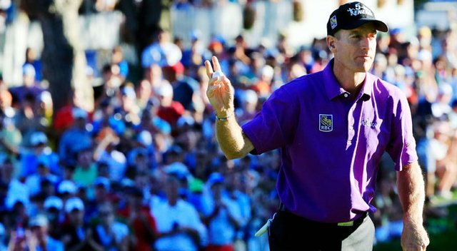 Jim Furyk celebrates after saving par on the 18th green to finish with a 2-under 68.