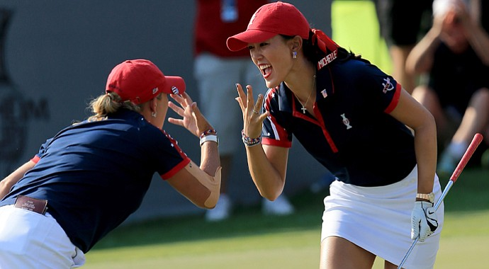 Michelle Wie of the U.S. celebrates holing a chip shot at the 13th hole in her match with Cristie Kerr against Charley Hull and Catriona Matthew during the afternoon four ball matches for the 2013 Solheim Cup.
