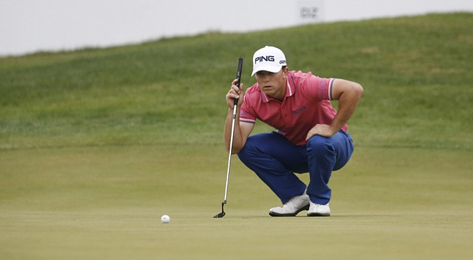 Luke Guthrie reads his putt on the 18th green during the second round of the BMW Masters. Guthrie leads by four shots.