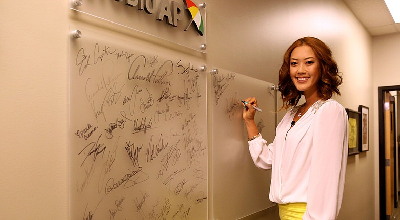 Michelle Wie signs the wall inside the Golf Channel studios during her first visit to the station on Friday.