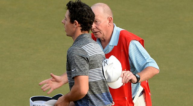 Rory McIlroy talks to caddie Dave Renwick on the 18th green after he was informed of a rules violation during the third round of the Abu Dhabi HSBC Golf Championship.