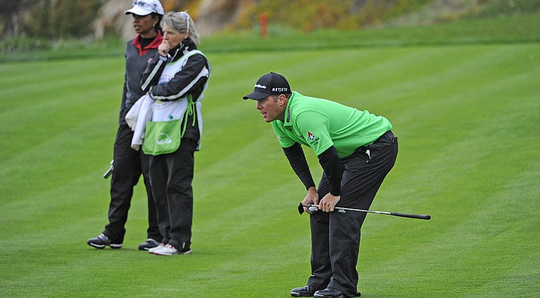 D.A. Points checks his line on the fifth hole at Pebble Beach Golf Links as Condoleezza Rice and her caddie watch Friday during the second round of the AT&T Pebble Beach National Pro-Am.