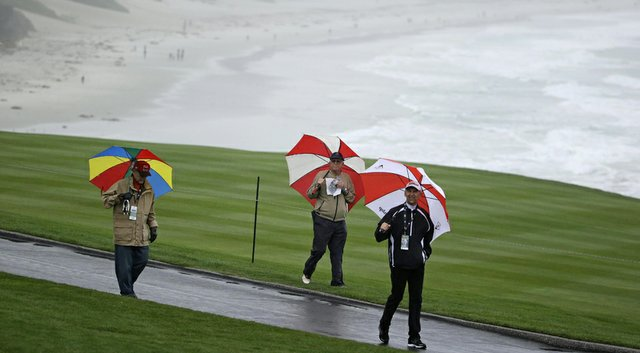 People walk in the rain along the ninth fairway of Pebble Beach Golf Links during the second round of the AT&T Pebble Beach Pro-Am.