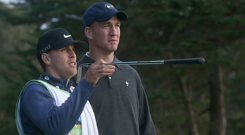 Denver Broncos quarterback Peyton Manning and his caddie talk over his tee shot on the sixth hole during the first round of the AT&T Pebble Beach National Pro-Am at Monterey Peninsula Country Club.