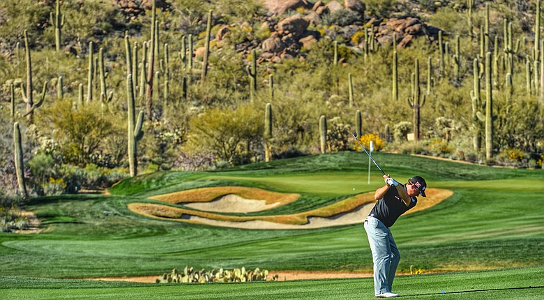 (Note: This image has been created with the use of digital filters) Graeme McDowell plays a shot during practice prior to the start of the WGC-Accenture Match Play at the Golf Club at Dove Mountain.