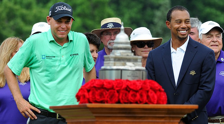 Winner Bill Haas and tournament host Tiger Woods smile during the trophy ceremony at Congressional Country Club in 2013.