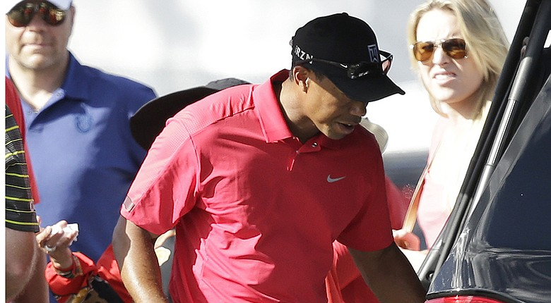 Tiger Woods reaches into an SUV after withdrawing during Sunday's final round of the PGA Tour's 2014 Honda Classic at PGA National in Palm Beach Gardens, Fla.