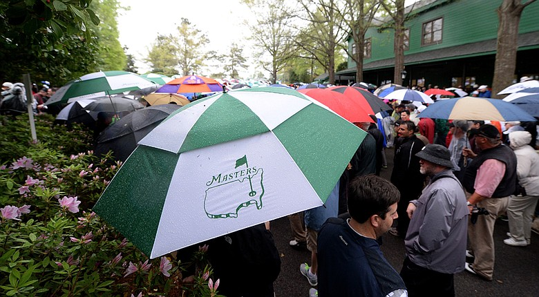 Patrons carrying umbrellas are evacuated from the course after play was suspended due to weather on Monday at Augusta national.