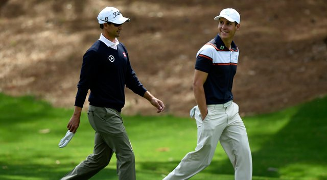 Adam Scott and Oliver Goss (right) walk together during a practice round prior to the start of the 2014 Masters.