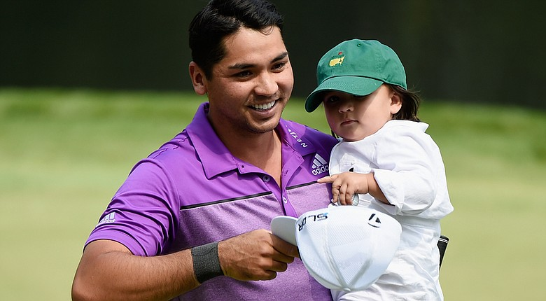 Jason Day walks with his son, Dash, during the Par 3 Contest prior to the start of the 2014 Masters.