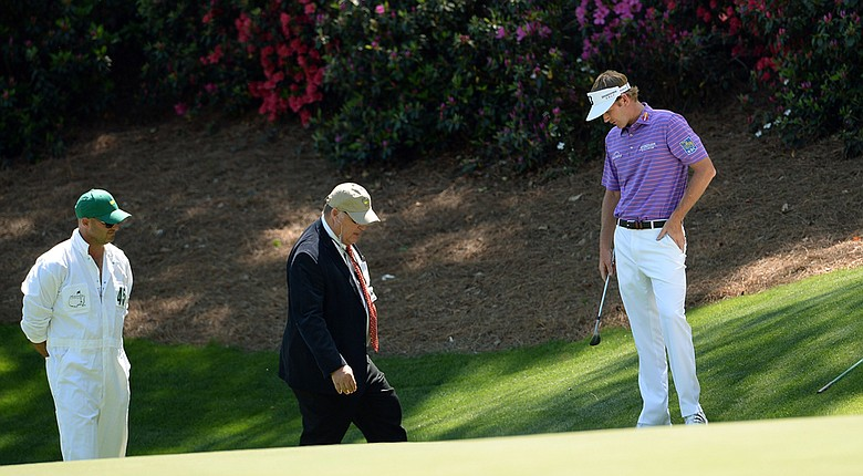 Brandt Snedeker speaks with a rules official on the side of the 13th green, where his ball moved during a pair of practice swings. Snedeker had to take a one-shot penalty, but still managed to par the hole.