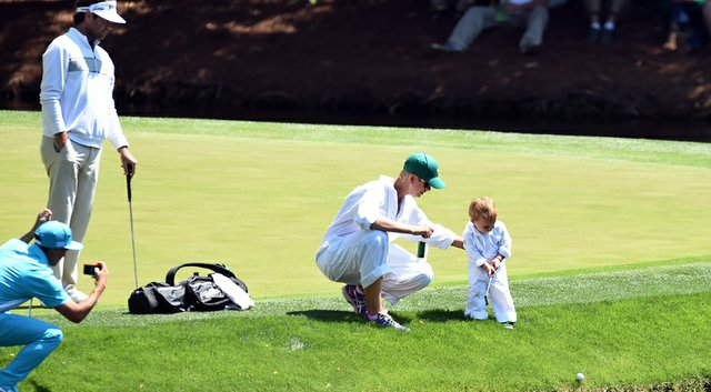 Rickie Fowler (bottom left) helps the Watson family chronicle the Par 3 Contest on Wednesday, with Caleb, 2, hitting his own shot down into the water.