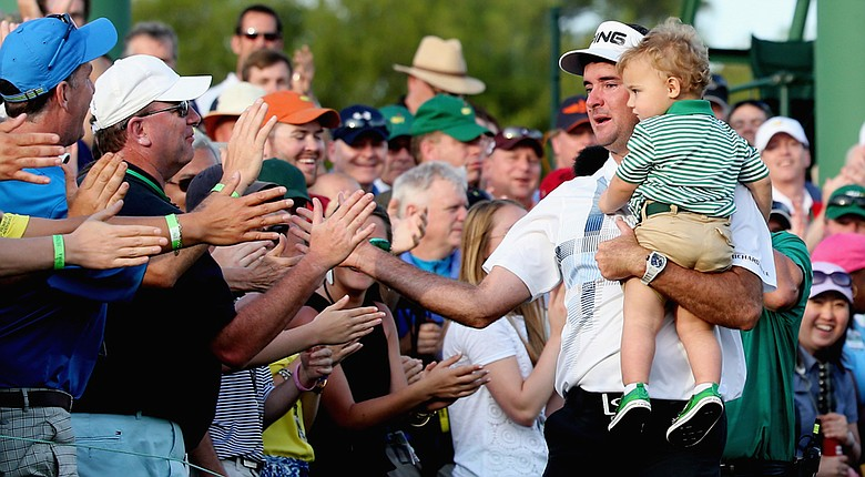 Bubba Watson holds his 2-year-old son, Caleb, while they celebrate with fans lining the 18th green after his three-shot victory at the Masters.