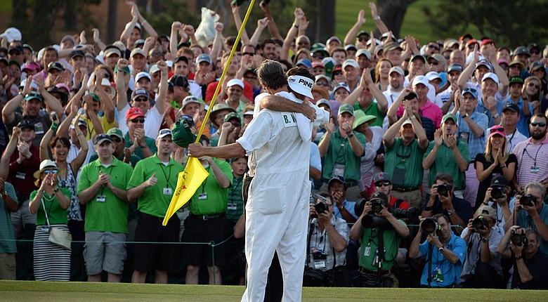 Bubba Watson embraces caddie Ted Scott after securing a three-shot victory at the 2014 Masters.