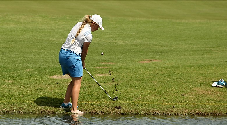 UCLA's Bronte Law spared her shoe from a shot on wet ground during Tuesday's first round of the NCAA Division I Women's Championship in Tulsa, Okla.