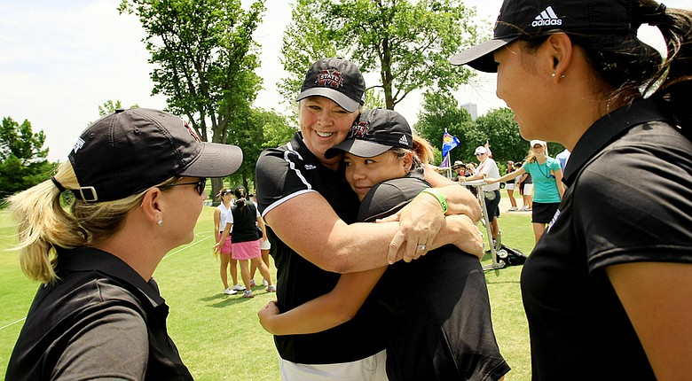 Mississippi State head coach Ginger Brown-Lemm hugs Rica Tse after completion of the second round of the 2014 NCAA Division 1 Women's Golf Championships at Tulsa Country Club. At right is Ji Eun Baik, assistant coach, Leigh Phillips.