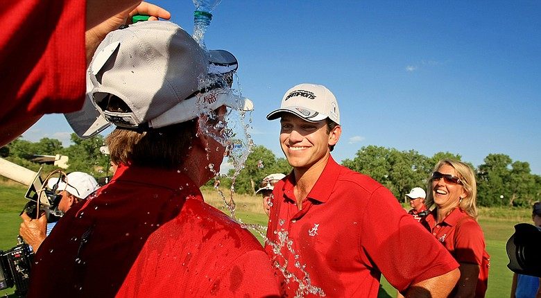 Alabama senior Cory Whitsett laps it up as head coach Jay Seawell gets doused with water after the Crimson Tide defeated Oklahoma State for the NCAA Men's Division I Championship on Wednesday at Prairie Dunes Country Club in Hutchinson, Kan.
