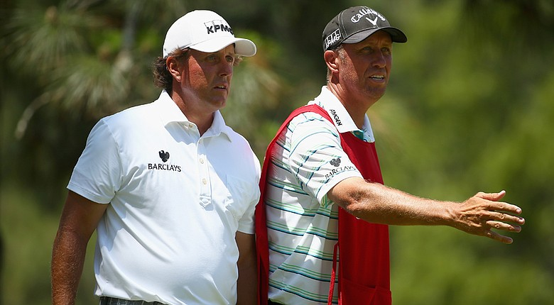 Phil Mickelson lines up a shot with his caddie Jim Mackay on the second tee during the third round of the U.S. Open at Pinehurst No. 2.