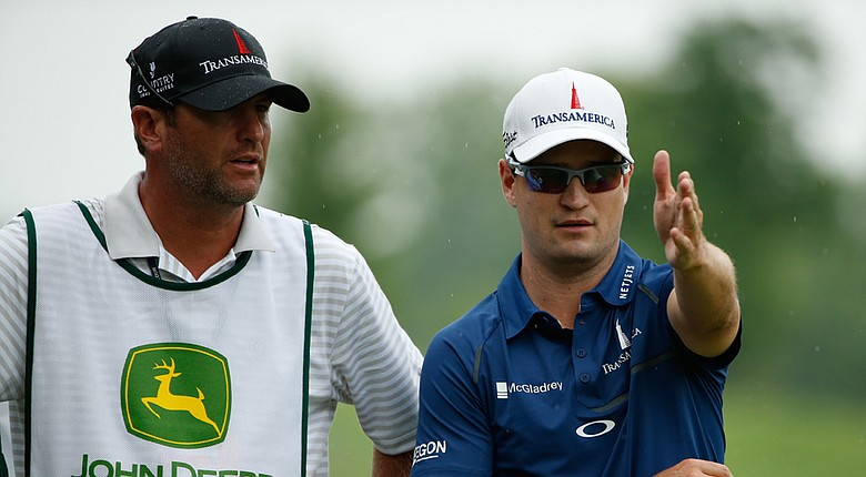 Zach Johnson works with fill-in caddie Lance Bennett during Friday's second round of the PGA Tour's 2014 John Deere Classic.