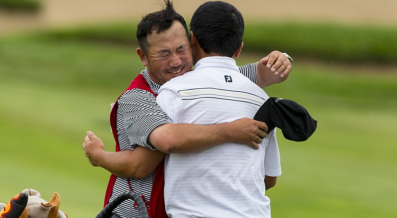 Doug Ghim, right, gets a big hug from his caddie/father, Jeff, after Doug beat Jordan Niebrugge in 23 holes at the 2014 Amateur Public Links.