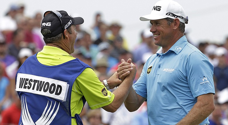 Lee Westwood (right) shakes hands with his caddie, Billy Foster, after firing a 6-under 65 at the 2014 PGA Championship.