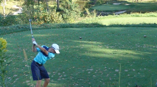 Drew Wrightson hits his approach on one of Wolf Run's picturesque par-3 holes.