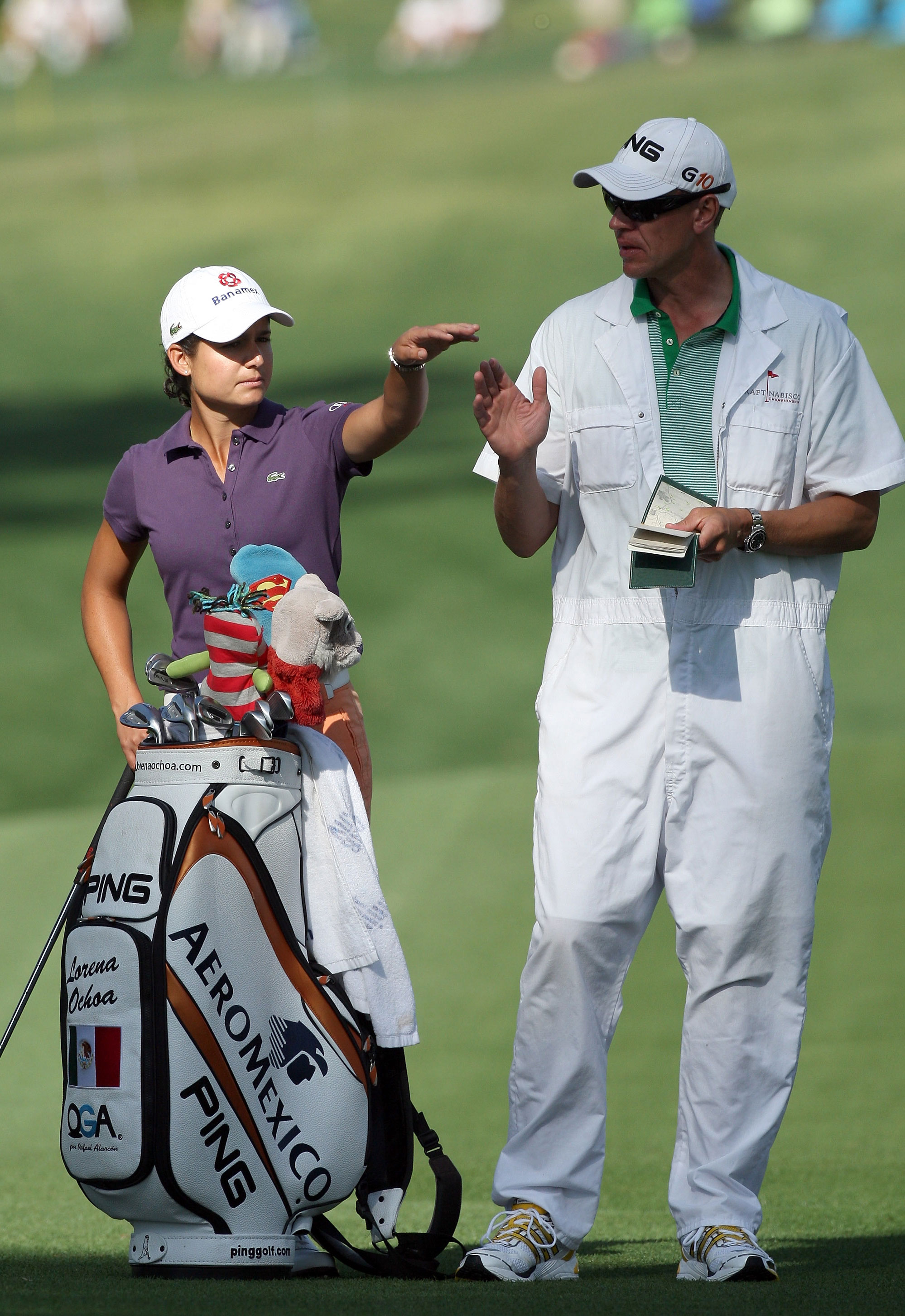 Lorena Ochoa of Mexico talks with her caddie Dave Brooker before she plays her second shot at the 12th hole during the first round of the Kraft Nabisco Championship.