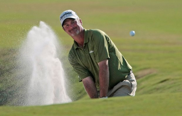 Jerry Kelly hits from a fairway bunker on the 18th hole during the third round of the Zurich Classic.