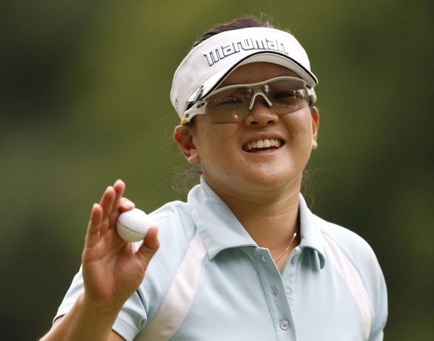 Eunjung Yi of South Korea waves to fans after making a birdie putt on the 17th green during the third round of the Jamie Farr Owens Corning Classic.