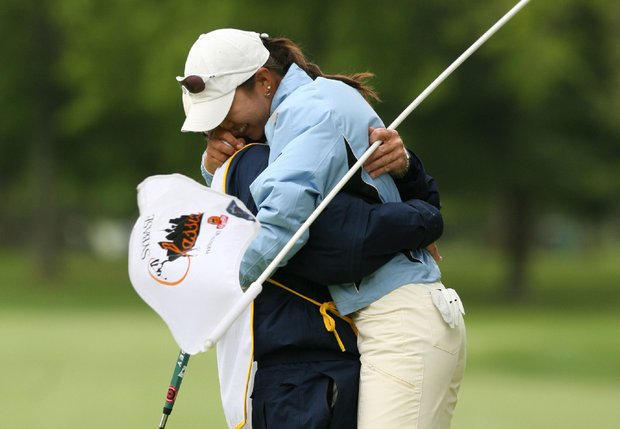 Ji Young Oh (R) of South Korea hugs her caddie after holing out on the 18th green to win the Sybase Classic.