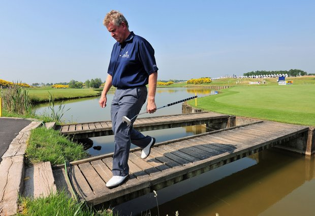Colin Montgomerie of Scotland walks across a bridge on the 18th hole during the first round of the Open de France.