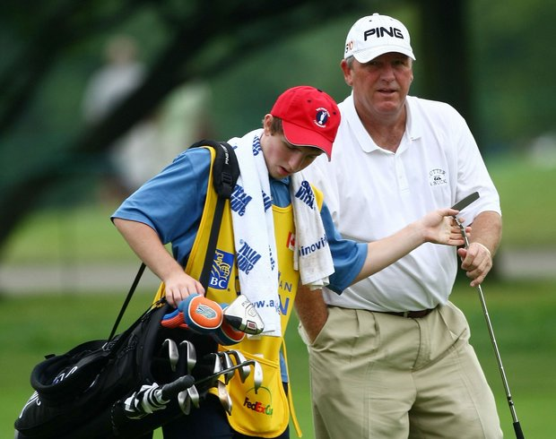 Mark Calcavecchia is handed his putter by son Eric Calcavecchia as they walk to the ninth green during round two of the RBC Canadian Open.