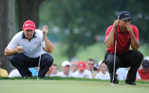 Padraig Harrington and Tiger Woods line up their putts on the 12th hole during the final round of the World Golf Championships-Bridgestone Invitational.