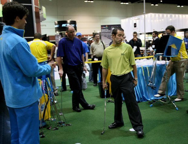 PGA Show participants compete for a putter at the Groove Equipment Ltd. booth at Orange County Convention Center in Orlando in January 2009.