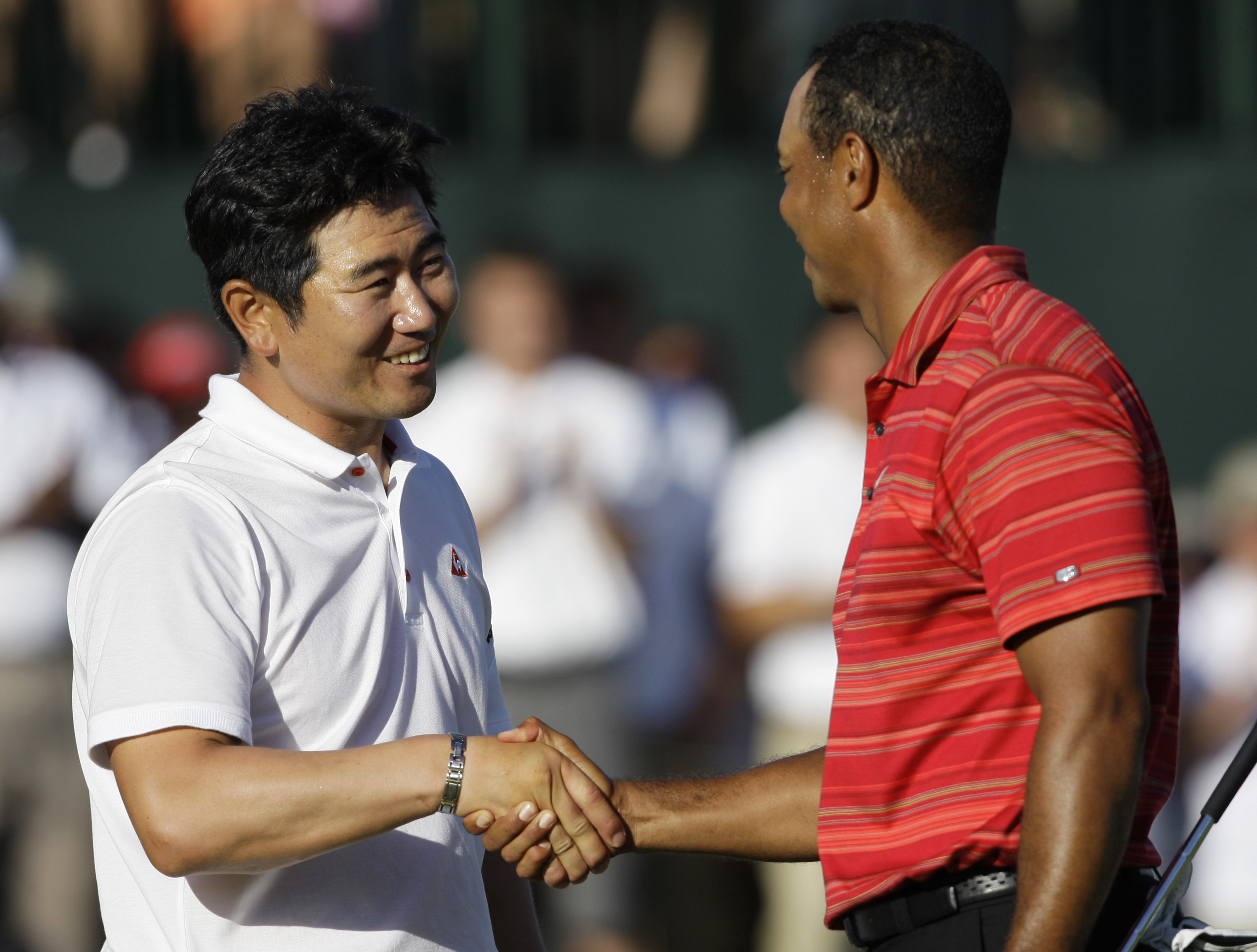 Y.E. Yang shakes the hand of Tiger Woods after defeating him at the PGA Championship.
