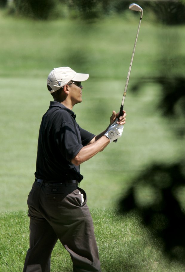President Obama follows through on a swing while playing golf on the second hole of the Farm Neck Golf Club.