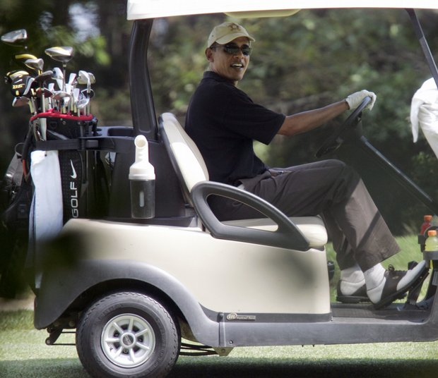 President Obama looks out from his golf cart while playing on the second hole at the Farm Neck Golf Club, in Oak Bluffs, Mass.