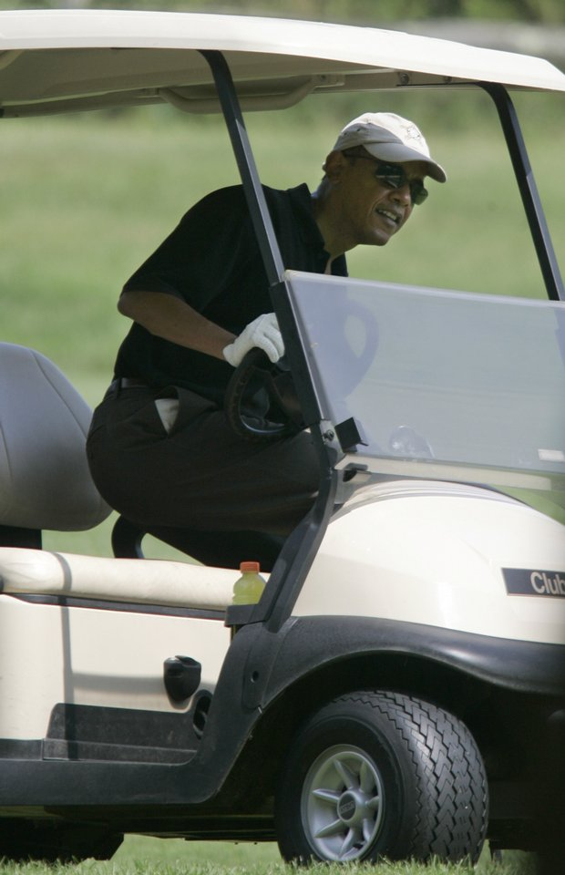 President Barack Obama steps into a golf cart while playing golf on the second hole of the Farm Neck Golf Club, in Oak Bluffs, Mass.