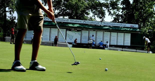 Players practice on the putting green during.
