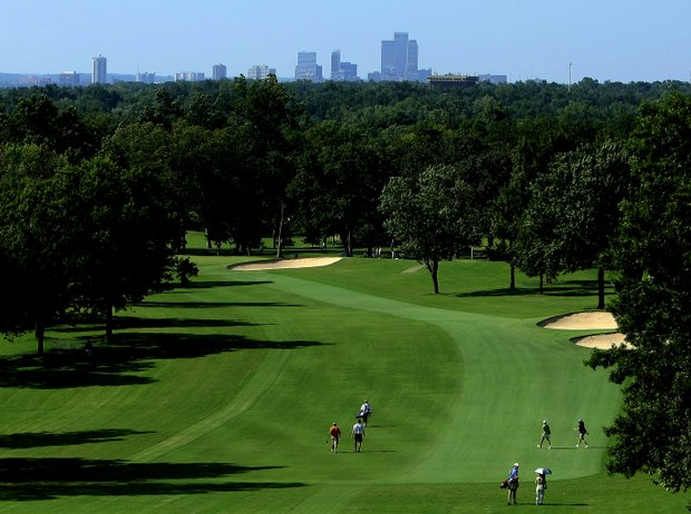 Golfers walk down the first fairway with the downtown Tulsa skyline in the background.
