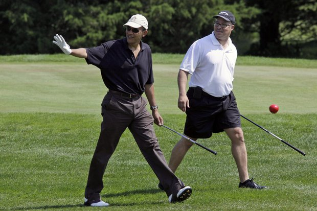 President Barack Obama waves as he walks with Dr. Eric Whitaker as they play golf during his vacation on Martha's Vineyard.