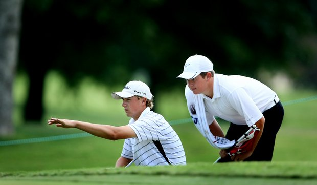 Jordan Spieth and his caddie Corbin Wallace look over a putt at no. 12.